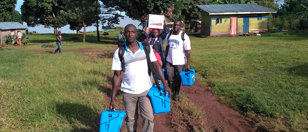 People carrying vaccine carriers and credo boxes in Uganda