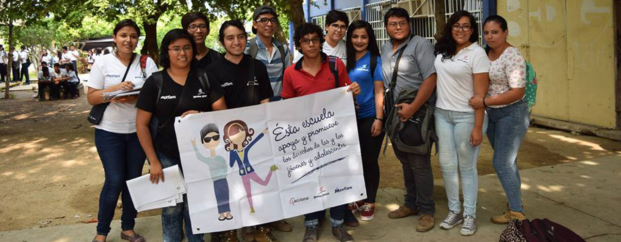 Group of people holding banner with 'This school supports and promotes the rights rights of young people and adolescents' written in Spanish