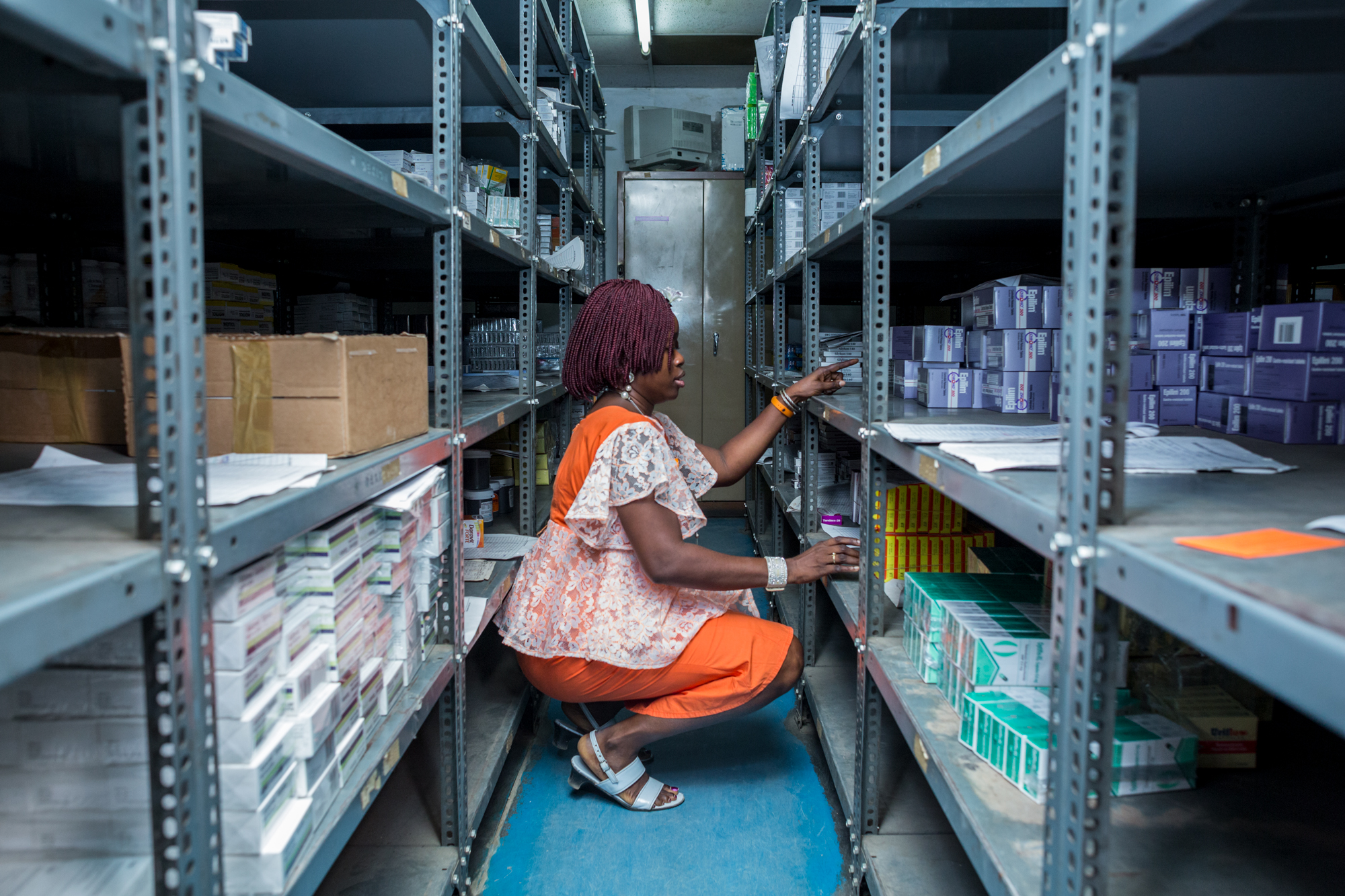 Pharmacist Adebisi arranges some drugs in the pharmacy store as she takes inventory. University College Hospital, Ibadan. Etinosa Yvonne © Wellcome Trust WOMAN_TRIAL_