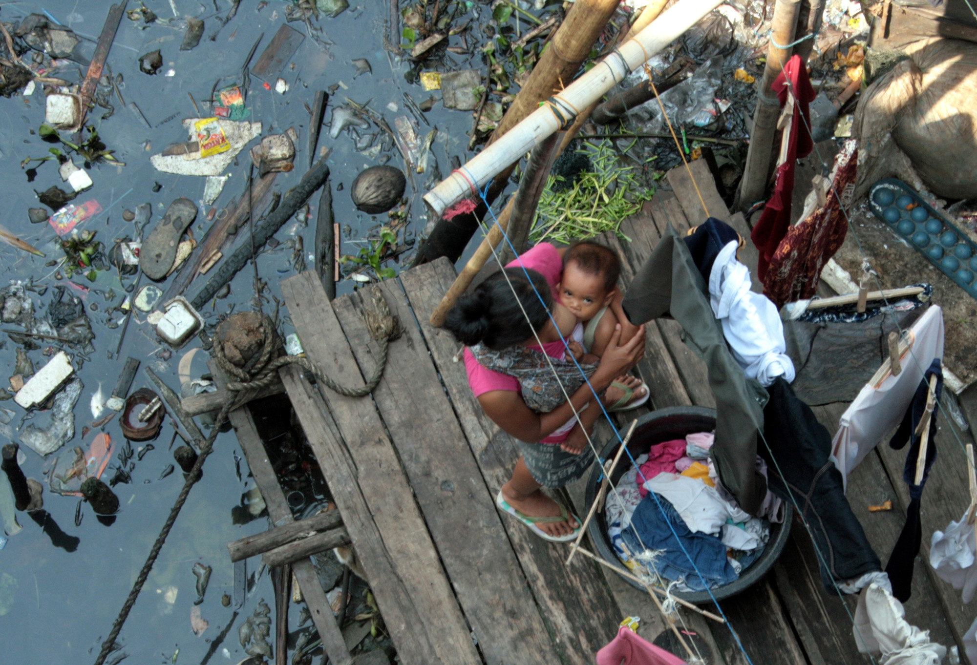 A mother breastfeeds her baby as she washes laundry behind her house on the banks of a polluted river in North Jakarta, Indonesia. Credit: 2007 Bunga Sirait, Courtesy of Photoshare