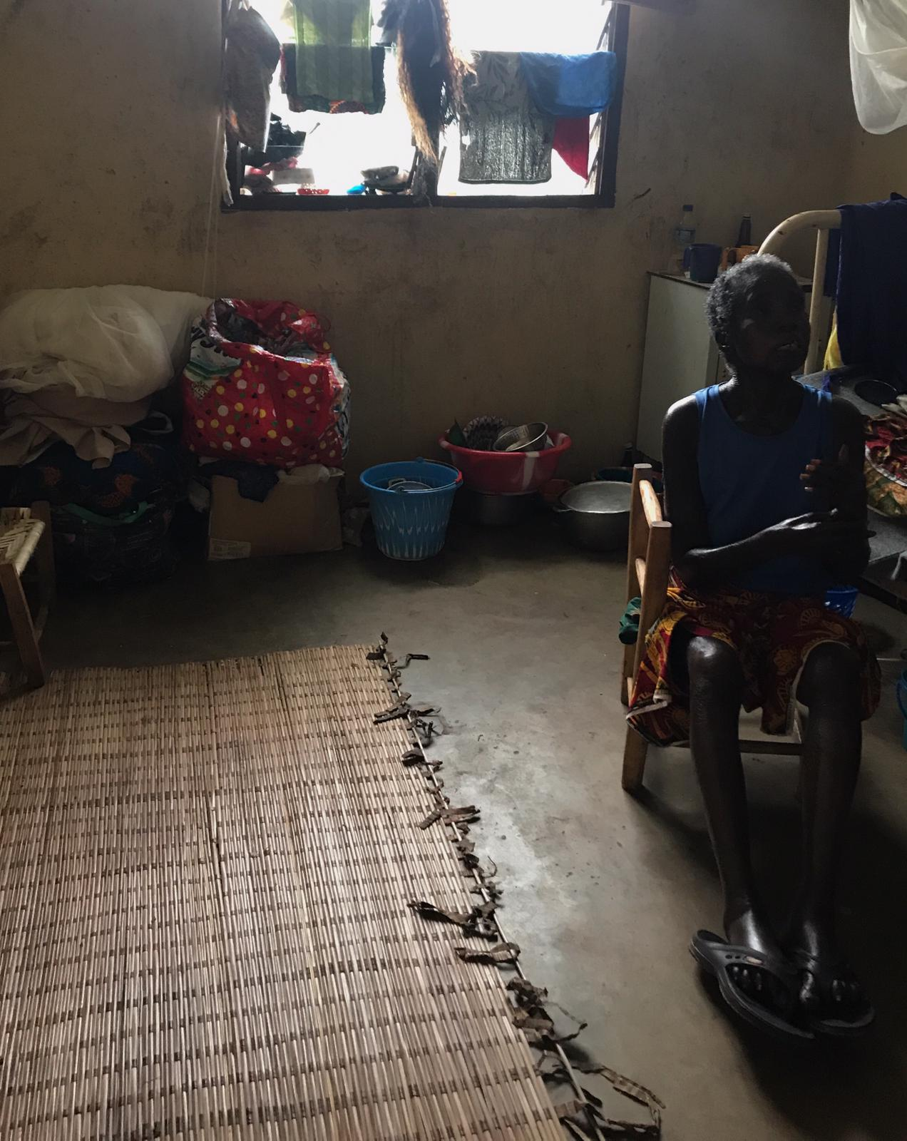 A woman affected by leprosy sits in her room within the rehabilitation centre after explaining her experiences with stigma and disability in the community. People affected by leprosy need to take long courses of multidrug therapy, for which they stay as in-patients for over one year.