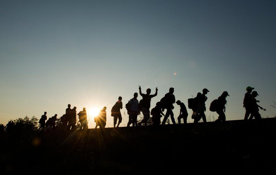 Migrants walking by sun