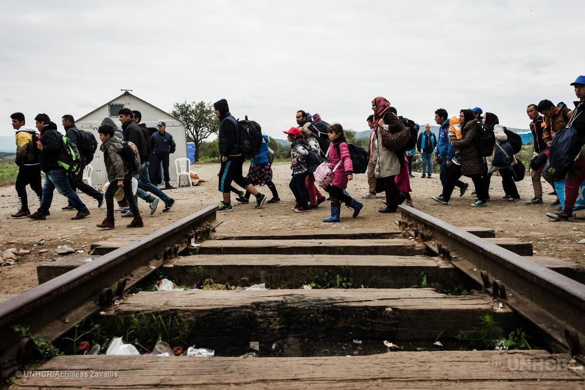 Migrants crossing train track