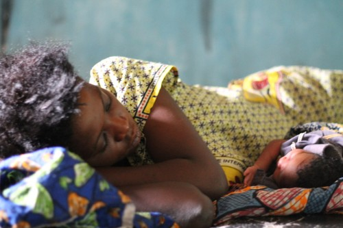 A woman lying down with her newborn at a maternity ward in Kasai Occidental, DRC.  Photo: Rishma Maini