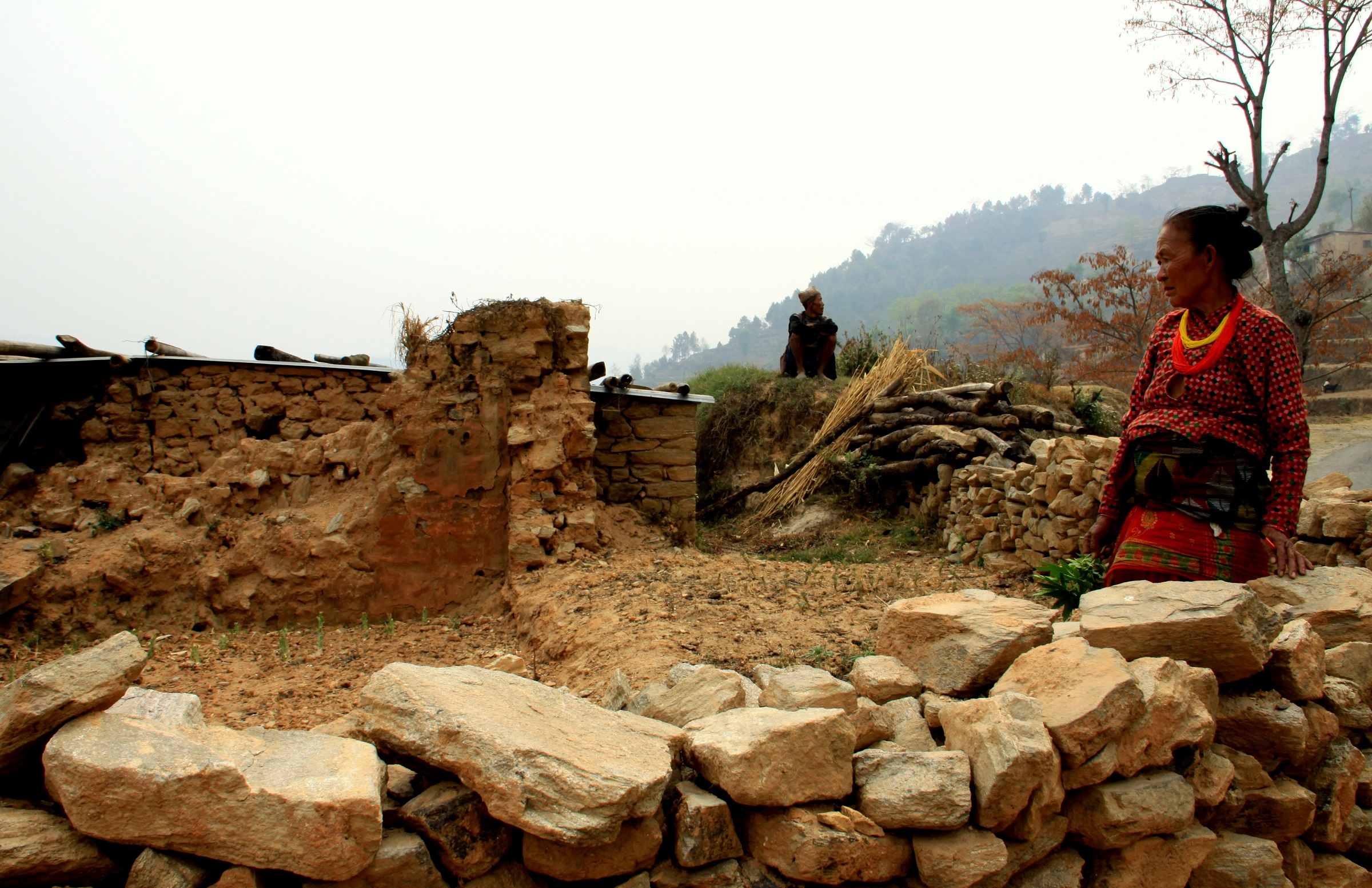 An elderly couple at the site of their house in Nanglebari, Nepal, that was destroyed by the 2015 earthquake. © 2016 Leesha Manju, Courtesy of Photoshare