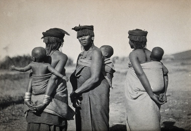 Africa: three women carrying babies on their backs in fabric slings. Photograph, 1910/1930: Credit Wellcome Collection [CC BY]