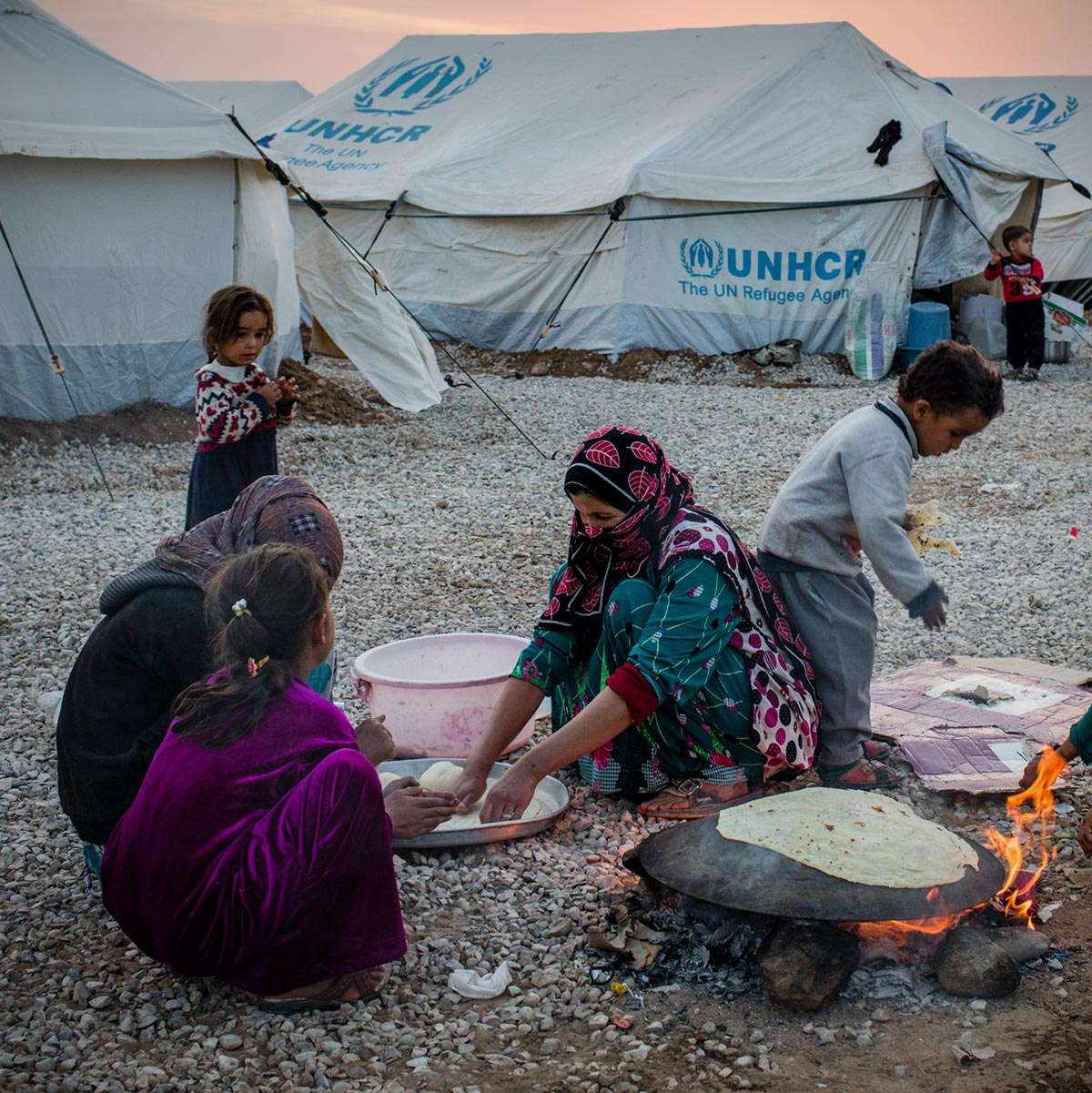 Mother bakes bread with children © UNHCR