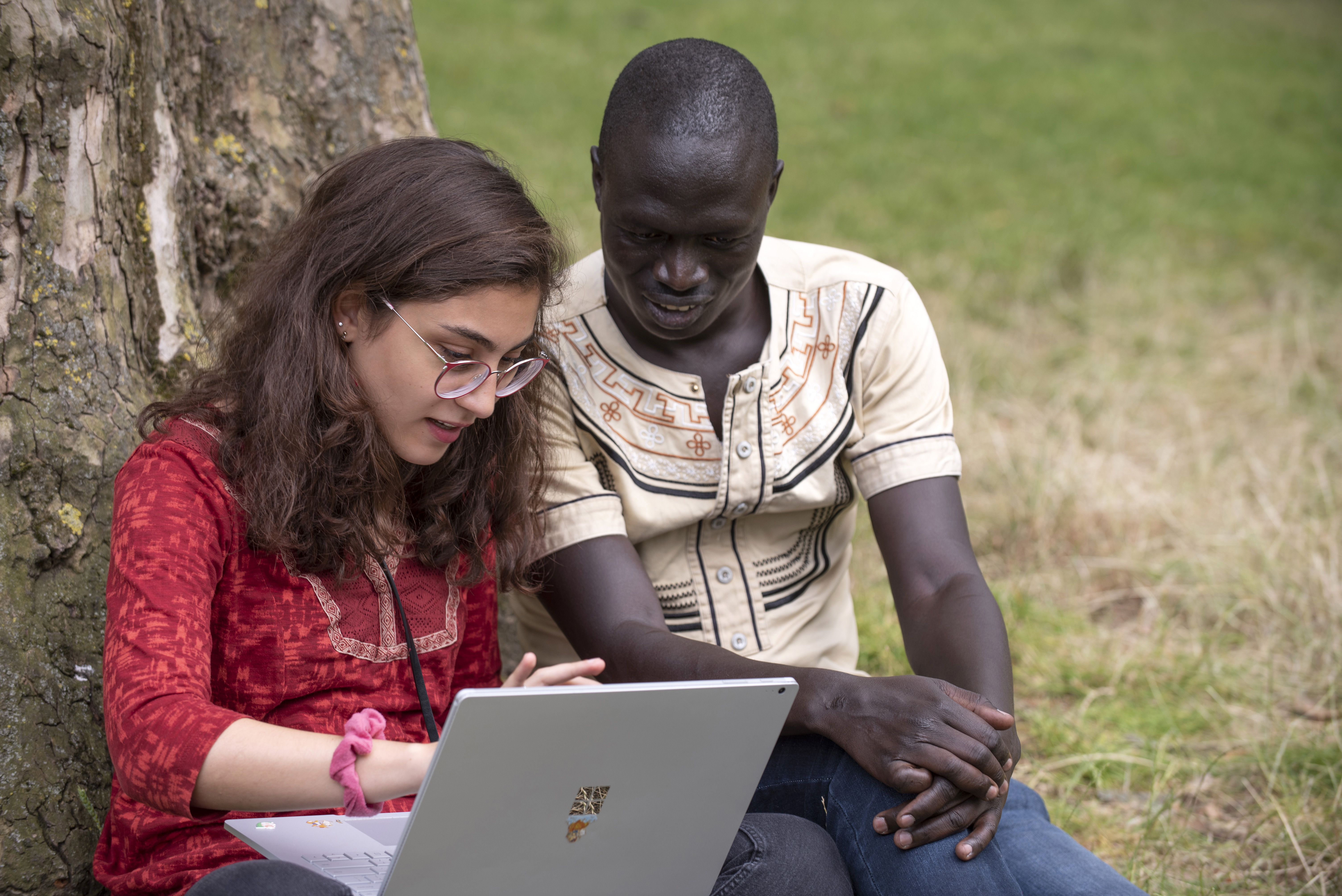 Two individuals looking at a laptop