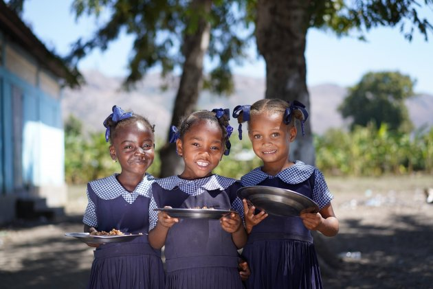 Three young girls in school uniform holding plates of food. Photo: WFP/Antoine Vallas
