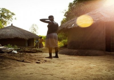 image of woman standing outside huts in uganda