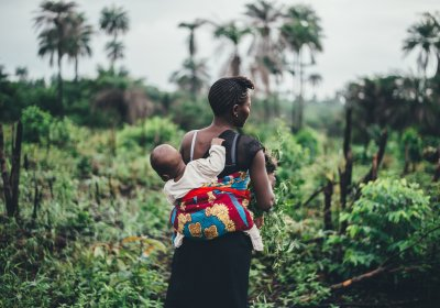 Mother carrying a young child on her back, shown from behind, in green fields in Sierra Leone