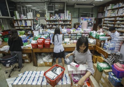 Pharmacists hurriedly prepare medicines to dispense in a general hospital, in Ratchaburi, Thailand