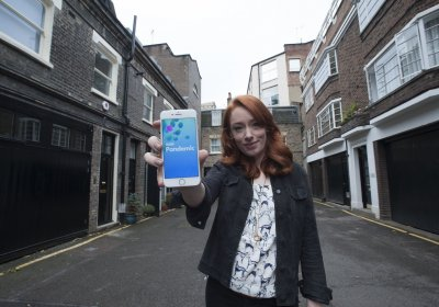 Hannah Fry holding a smartphone displaying the BBC Pandemic App. Credit: 360 Productions
