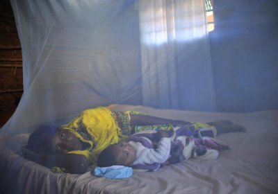 Leila Abdala, 30, with her baby Kairat, 5 months, lie under a bed net at their home in Mtwara, Tanzania