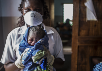 A nurse with face mask holding a newborn baby