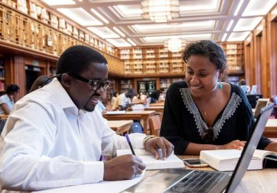 Two individuals sitting in the LSHTM library are looking over pieces of work