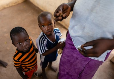 Two young boys wait to be given their does of anti-malarials, Basse, The Gambia. Credit: Louis Leeson/LSHTM