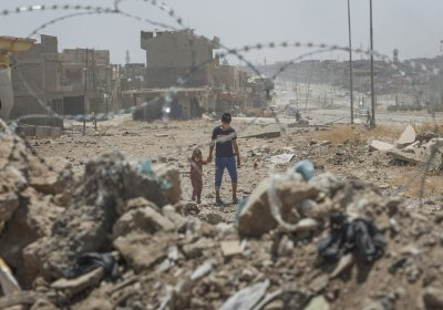 Young boy and small child behind barbed wire in Mosul