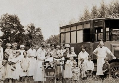 A mobile health unit, parked in a Pennsylvania field: women and their children are shown receiving treatment from the unit's health practitioners. Photograph, 1920/1930? Wellcome Collection