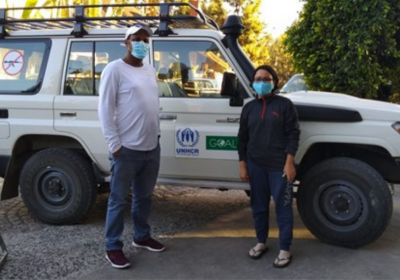 Ritu is with a colleague standing in front of a white jeep. They are both wearing face masks and socially distanced.