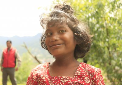 Young girl smiling outside her family home. Photo credit: International Centre for Evidence in Disability