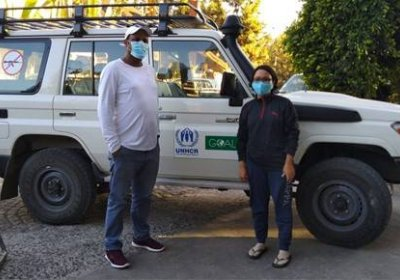 Ritu Rana and friend standing in front of a car wearing PPE