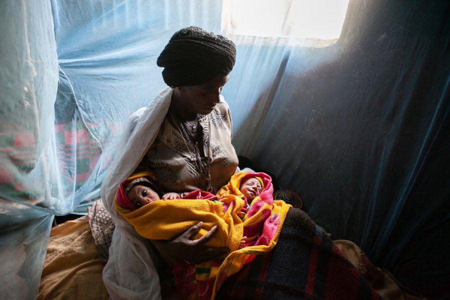 Newborn twins and their mother under a bednet in Ethiopia - Credit Paolo Patruno