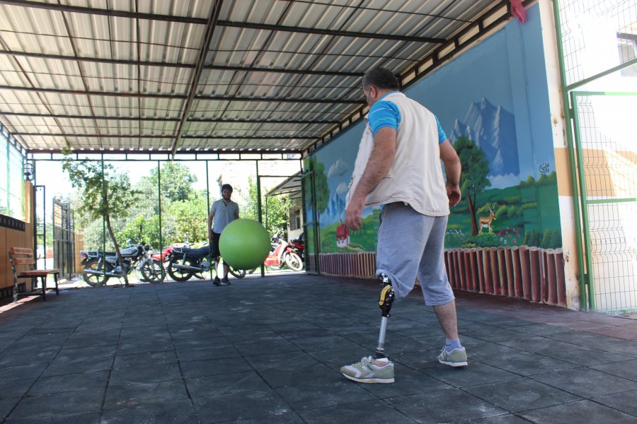 Two people with amputated legs kicking a ball