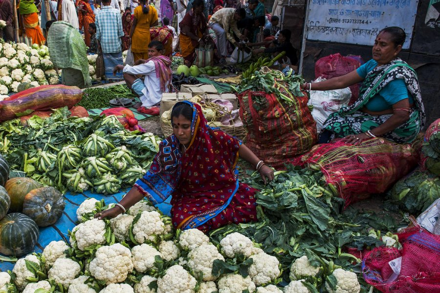 Women arranging vegetables to sell at a market in India