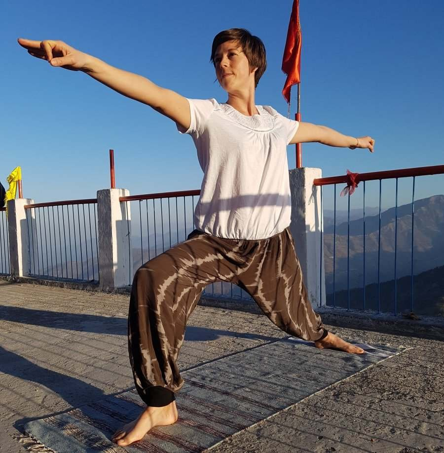 Female striking a yoga pose on a mat on the top of a mountain