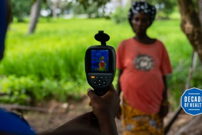 A field worker from MRC Unit The Gambia at LSHTM uses a thermal imaging camera to measure a mother and her unborn baby's temperature in Keneba as part of a study looking at the impact of heat stress on pregnant farmers. Credit: Louis Leeson/LSHTM