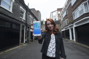 Hannah Fry holding a smartphone displaying the BBC Pandemic App
