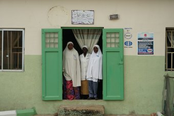 Three healthcare professionals at entrance to maternity ward, Gombe State Nigeria. Credit: IDEAS
