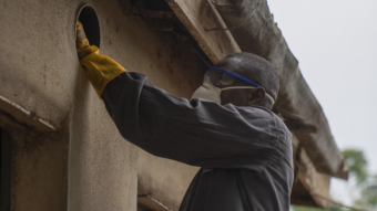 Man installing eave tubes for malaria control in Africa