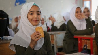 Aziza, seventh grade, eats a date bar in a classroom at Salah Al-Din School in Sana'a city. Credit: WFP/Ahmed Haleem