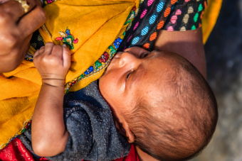 A baby being breastfed by her mother in Jaipur, India. The baby is central in the picture with the mother cropped at the shoulders, but she's wearing multicoloured clothing and a bright yellow shawl.