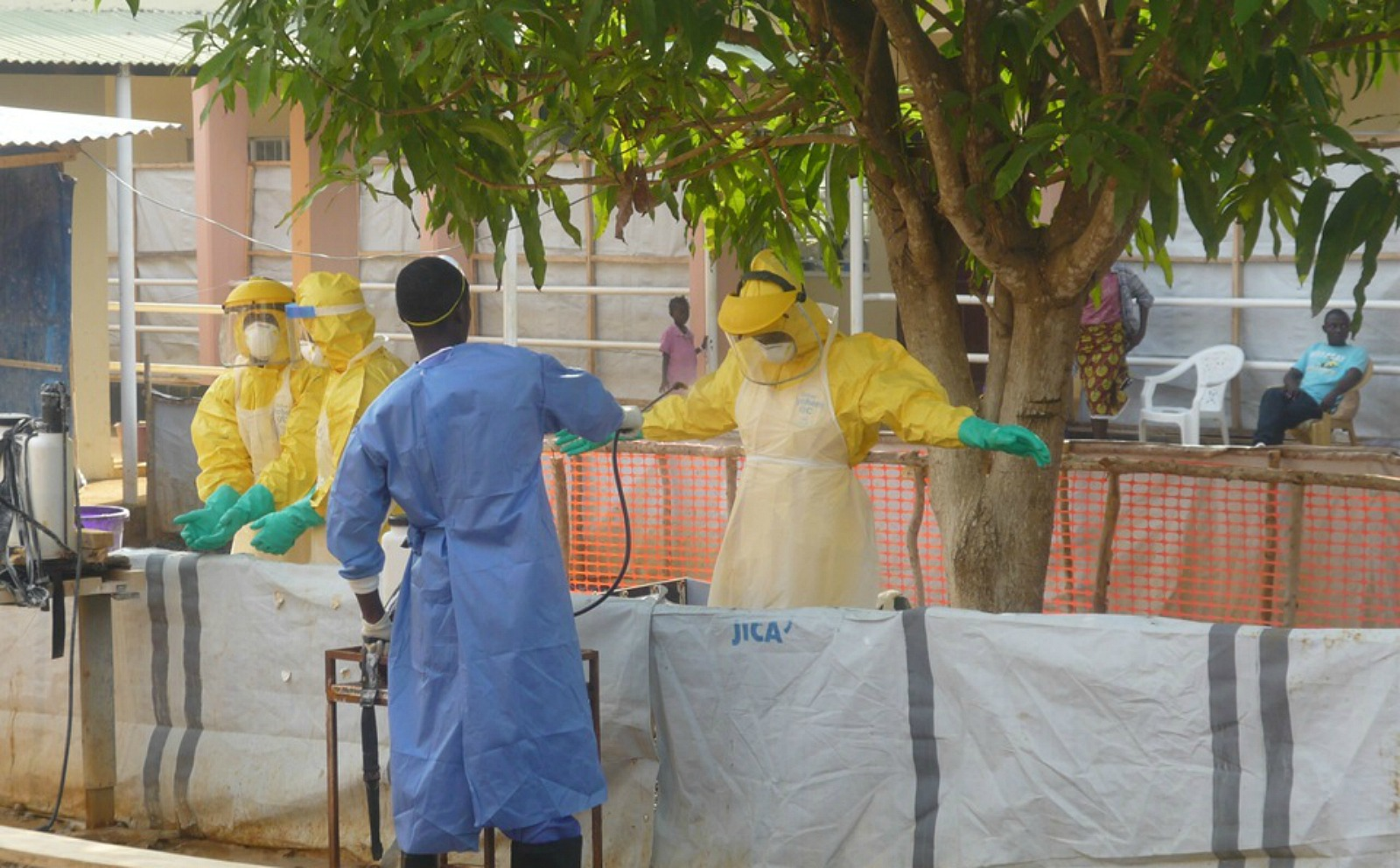 Health workers being hosed down by a fellow staff member.